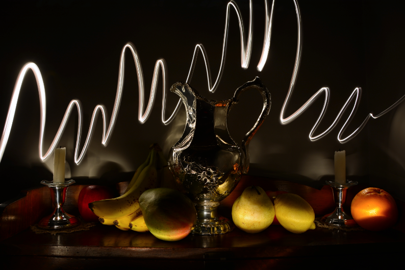 light portrait digital chiaroscuro photography modern contemporary shadow contrast blur distorted surreal multiple spotlight highlight streak flash zigzag fruit silver water pitcher fancy ornate engraved candlesticks white stubs candle orange pear mango bananas ripe red apple wooden table