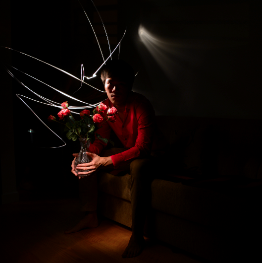 light portrait digital photograph dark light chiaroscuro contrast shadow streak flash line young asian man boy sitting couch sofa holding bouquet bunch flowers roses pink glass shirt button down