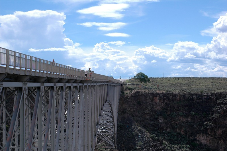 photograph of a bridge over a gorge dazzling sky bright blue cloud clouds formation ravine scary perspective deep hot summer daylight nature composition angle