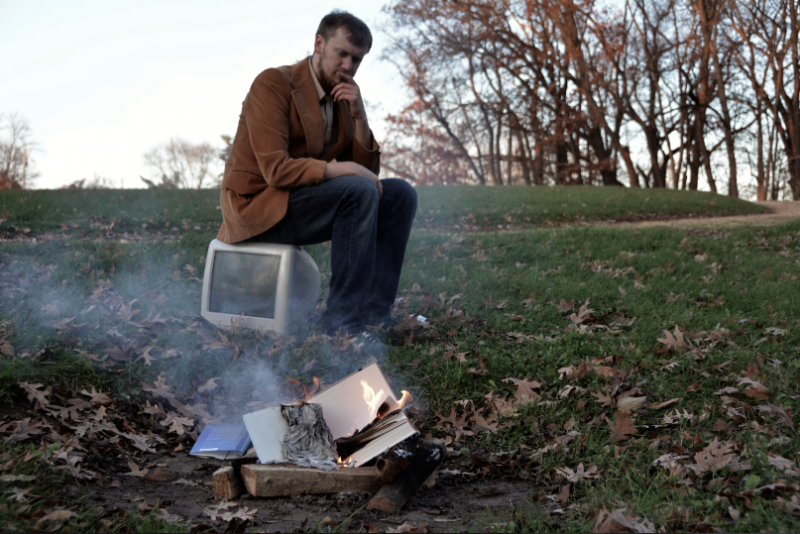 digital photograph young man pensive sitting on old white clear imac jeans computer brown corduroy jacket book pile heap smoke burning flames bonfire campfire thinking chin hand outdoors grass leaves autumn fall bare trees