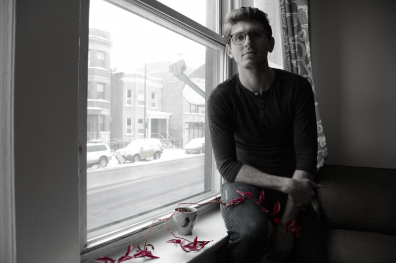 digital photograph portrait young man sitting on windowsill winter snow curtain jeans glasses plant vine red leaves mysterious accent color sepia black white