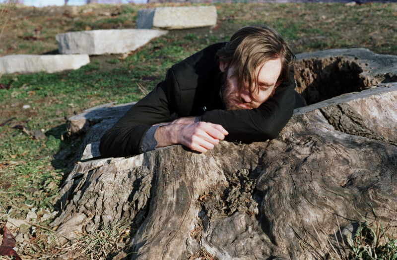 young man black jacket park nature woods giant big tree stump hollow inside napping