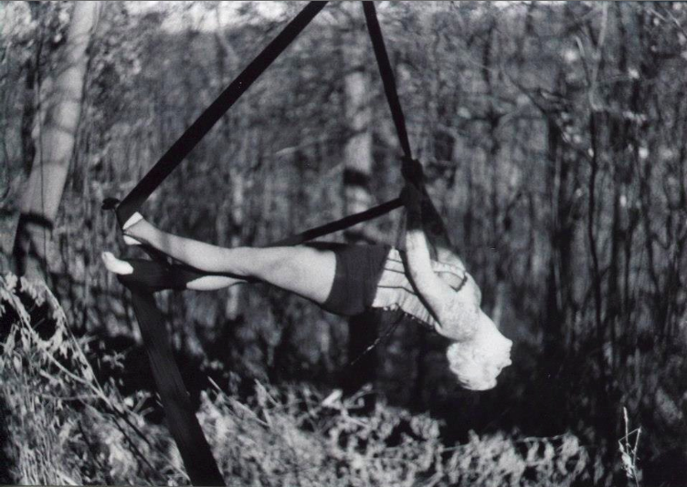 photograph of a girl posing on aerial silks tissu against a forest background blue corset blonde tattoos circus tricks suspension black and white