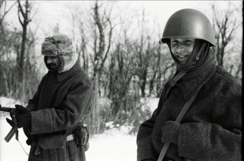 black and white film portrait photograph vintage retro WWII uniform young men winter snow smiling helmet fur hat