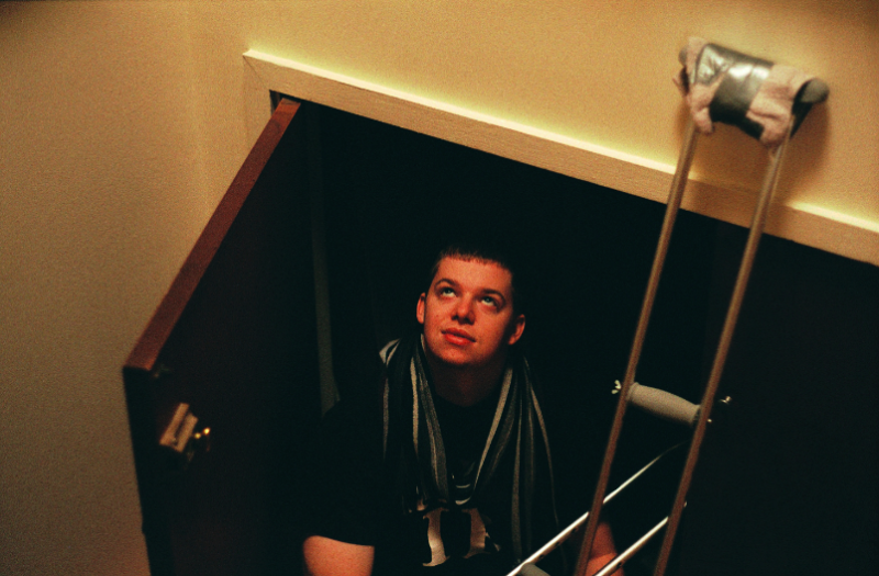 film photograph young man looking up crutches