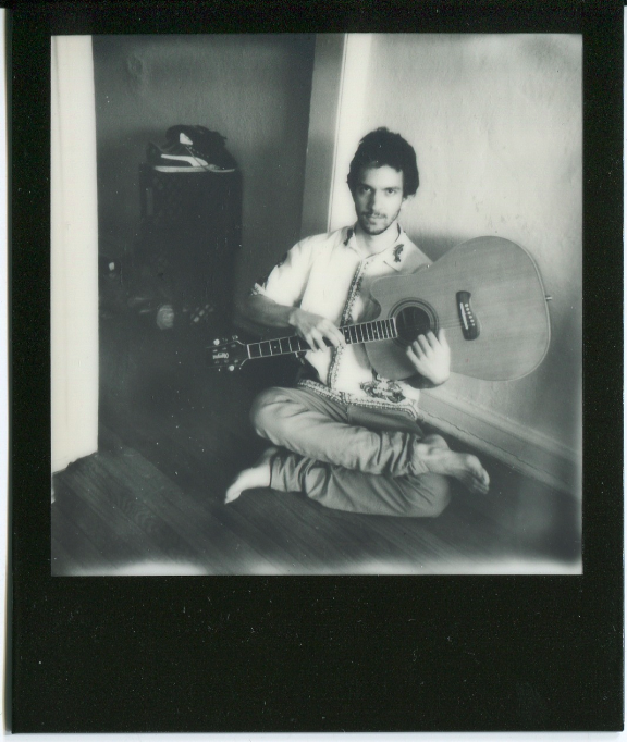 polaroid film vintage retro black white impossible project border young man guitar upside down crossed legged lotus sitting hippie 70's