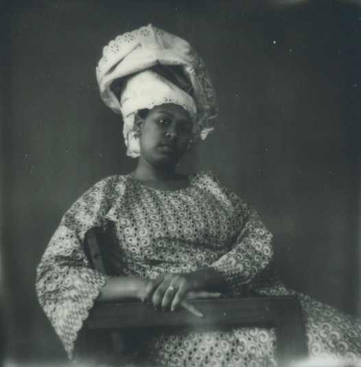 polaroid retro vintage film blurry grainy young lady girl african american sitting wooden chair traditional garment dress floral pattern headdress headscarf lace
