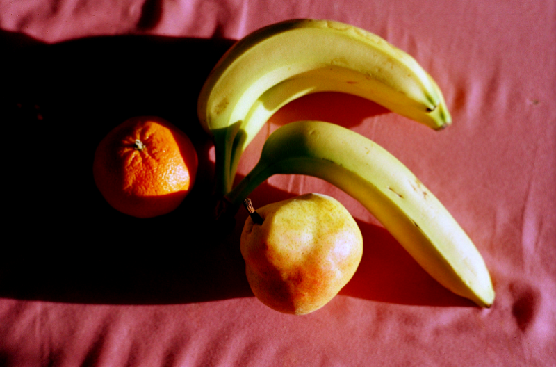 film photograph still life bananas orange pear clementine tangerine pink cloth shadow chiaroscuro contrast light