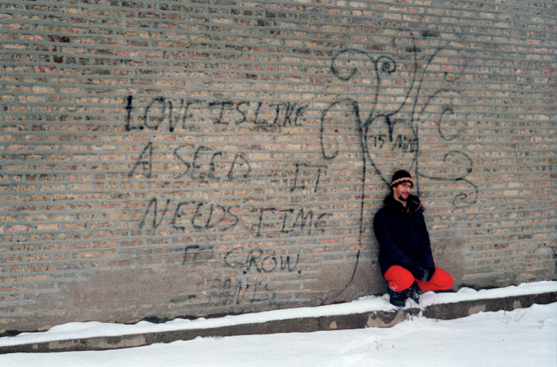 film vintage retro photograph brick wall graffiti love is like a seed it needs time to grow janis young man red pants squatting funny
