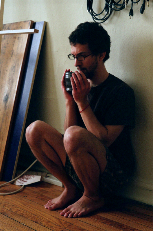 film photograph portrait vintage retro young man squatting crouching wall cup of tea hot pensive glasses