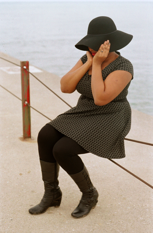 young african american woman girl sunhat black dress boots beach lake pier fashion covering head windy