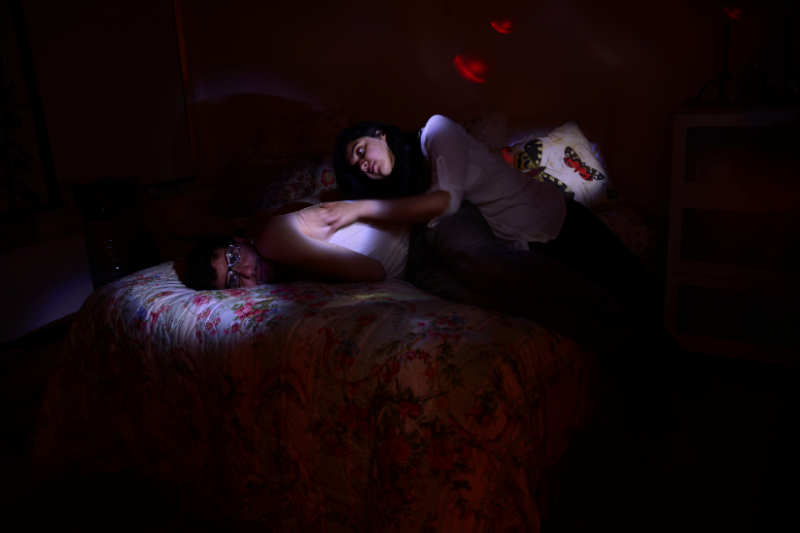 digital photograph portrait couple lying bed floral cover quilt pillow butterflies chiaroscuro shadow lighting surreal stroking affectionate glasses cuddle boy girl man woman