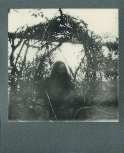 young man long hair red flowing beard hippie polaroid black and white branches bower