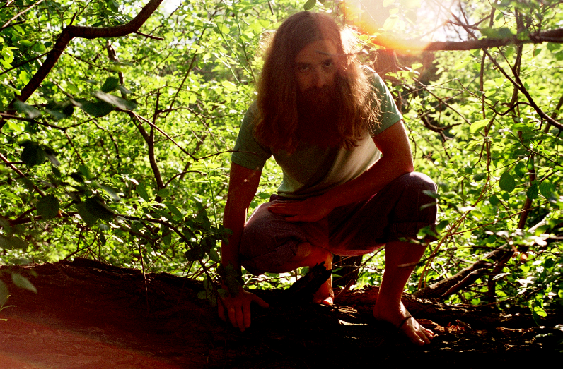 young man long hair red flowing beard hippie forest sun leaves light nature