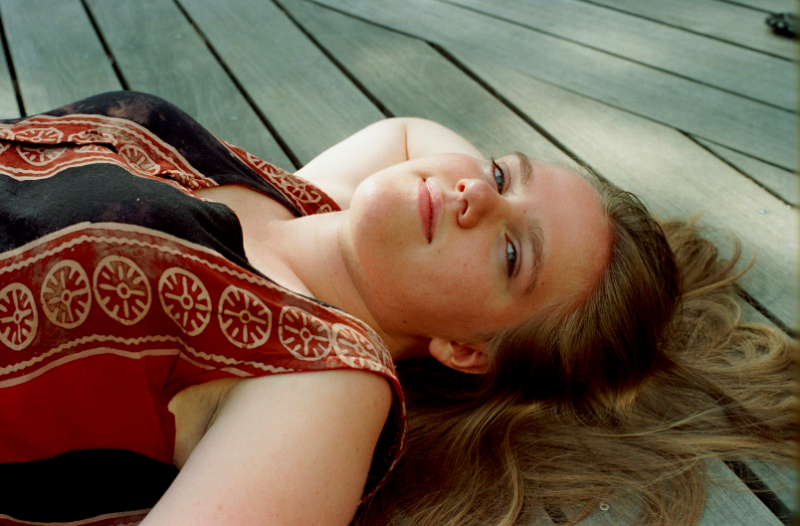 film photograph portrait girl lying wooden planks blue eyes dirty blond