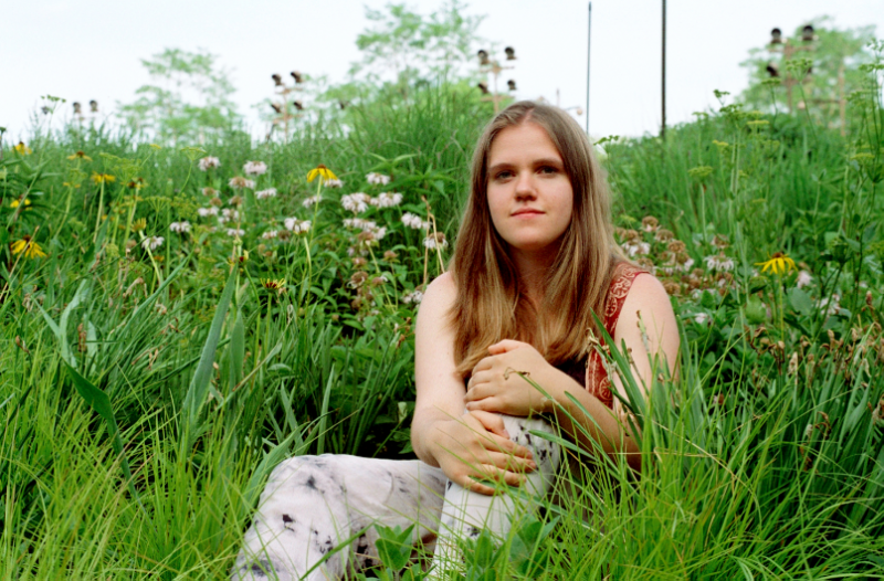film photograph portrait girl sitting meadow grass flowers colorful nature outdoors park