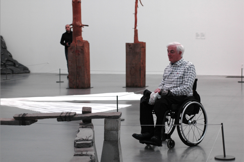 man in a wheelchair in a room with modern art installations muted gazing hiding pillar staring composition light shadow falling