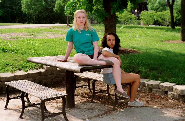 film photograph portrait young woman pair blonde brunette sitting picnic table