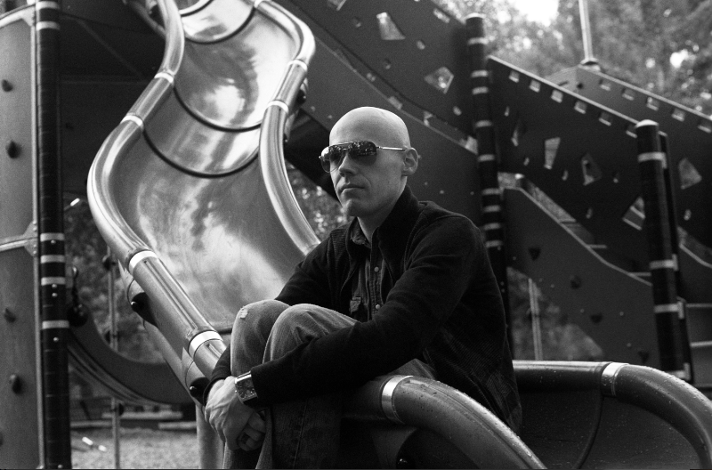 film photograph portrait black white playground man sitting slide sunglasses