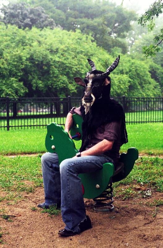 film photograph portrait sitting playground equipment dinosaur man goat mask creepy