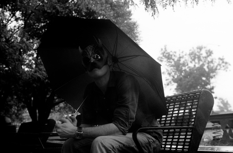 film photograph portrait black white umbrella man sitting bench shadows face mask mysterious