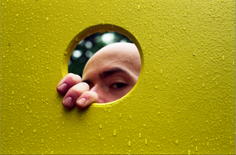 film photograph portrait playground man yellow rain water droplets eye peering hole