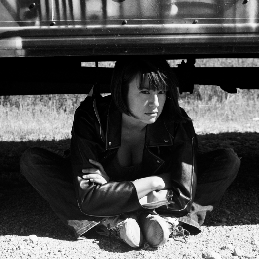 film photograph portrait young woman sitting crouching under truck