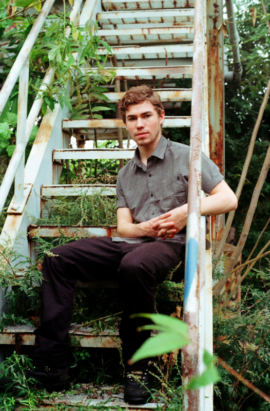 portrait young man boy sitting steps abandoned weeds grass