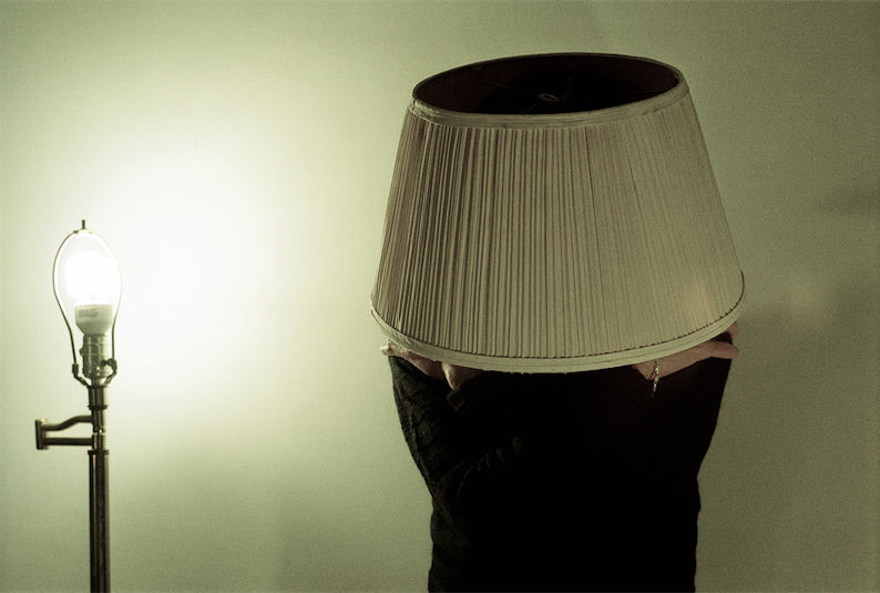 film photograph surreal lightbulb lamp bare lampshade person woman wearing covering head black sweater