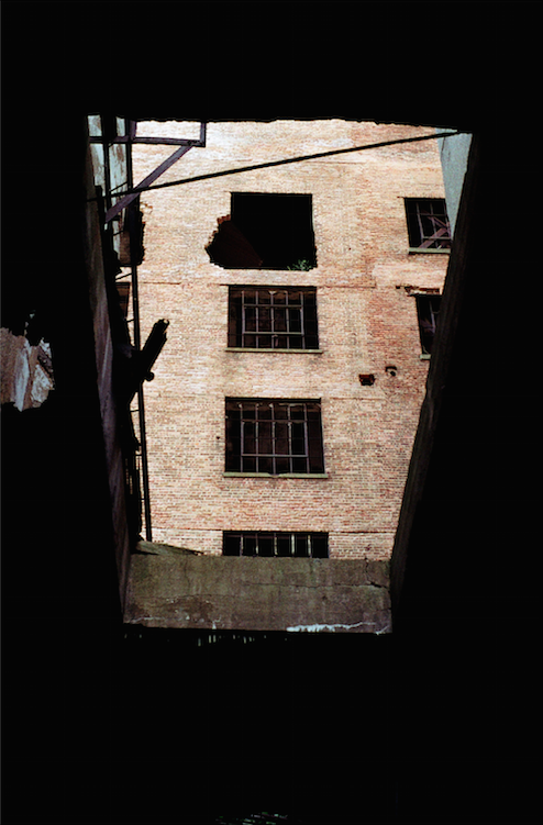 abandoned building factory shadows broken window looking up upshot roof hole perspective