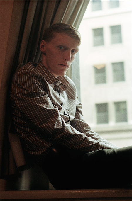 film photograph portrait young man blond proper tie button down shirt office sitting window seat curtain
