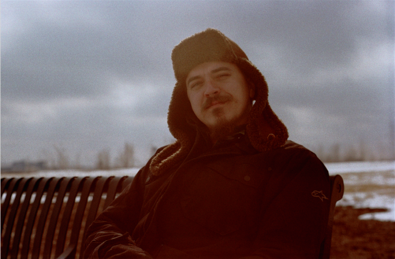 film photograph portrait young man goatee beard mustache sitting bench winter hazy sky russian cap hat earflaps pensive