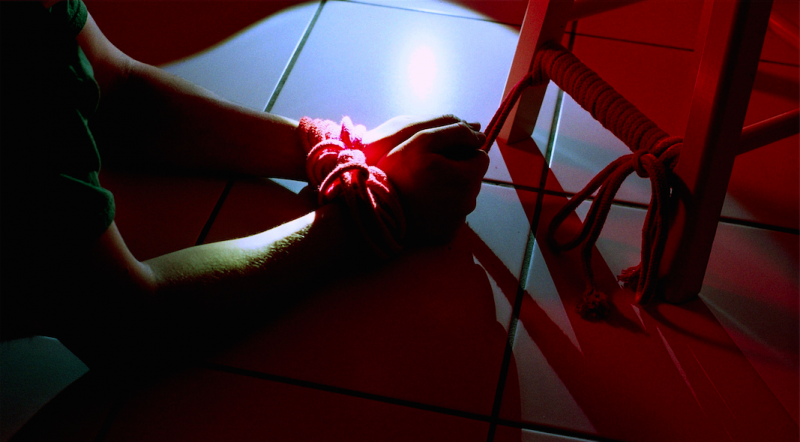 film photograph chiaroscuro light portrait darkness hands stool kitchen floor white tiles tied red rope shibari bondage