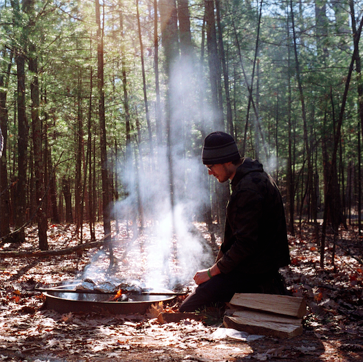 film photograph portrait camping fire pit smoke chiaroscuro young man sitting tending peaceful