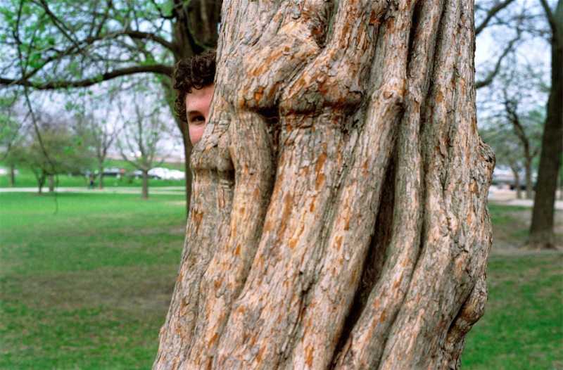 film photograph portrait park tree trunk young man boy hiding peeking lurking