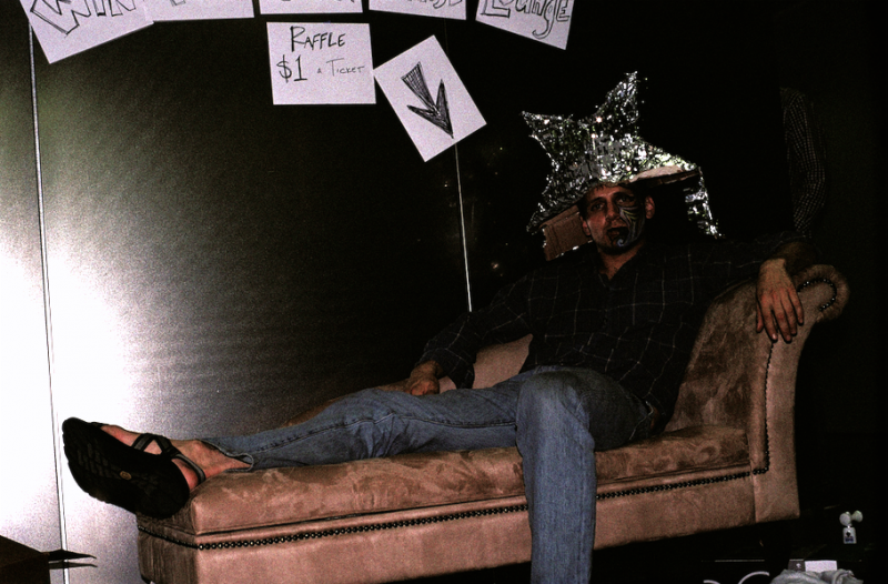 film photograph portrait young man party sitting couch pinata silver star hat head facepaint turnt