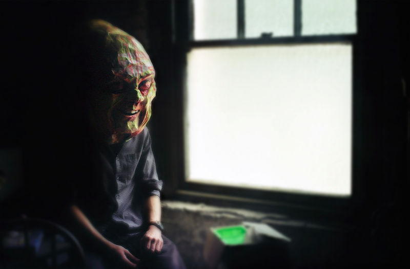 film photograph portrait bokeh surrealist basement window lawn chair seated dark shadowy mysterious person man sitting giant mask head creepy smiling grinning
