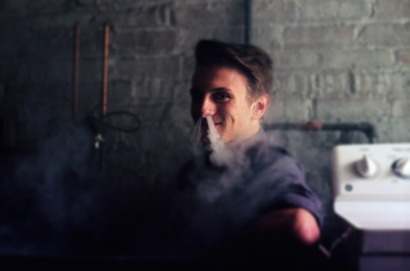bokeh film photograph portrait young man smoke nostrils dragon smile exhale vape