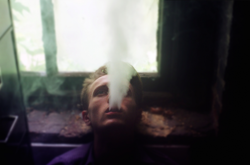 bokeh film photograph portrait young man smoke vape cloud exhale column mysterious