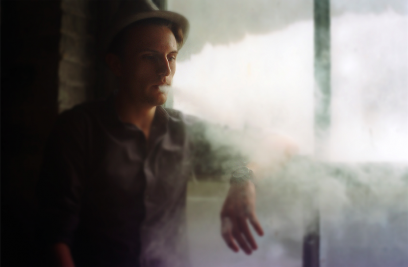 bokeh film photograph portrait young man smoke vape fedora watch dreamy mysterious