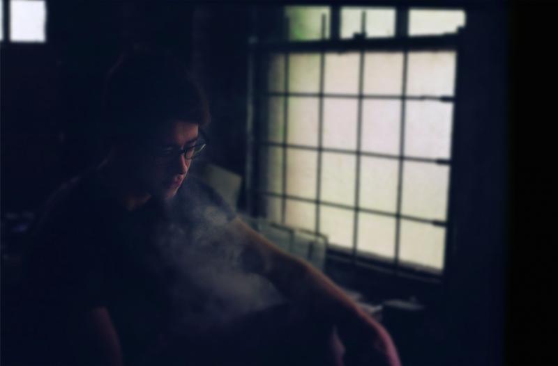 bokeh film photograph portrait young man smoke vape dark chiaroscuro window