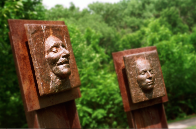 film photograph nature park sculpture faces laughing crying metal