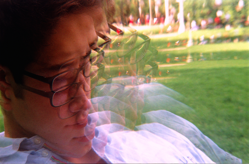 film photograph trippy psychedelic prism lens  portrait young man park outside glasses