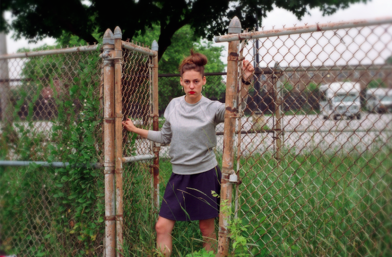 film photograph portrait young woman outside chain link fence fashion pose