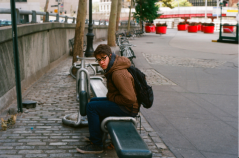 film photograph portrait young man sitting backpack