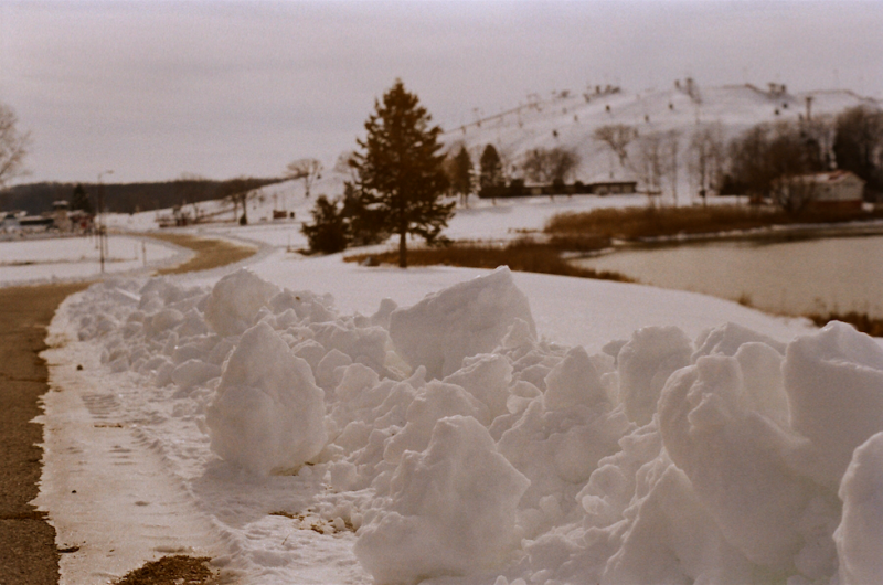film photograph snow winter chunks clumps road evergreen tree ski slopes