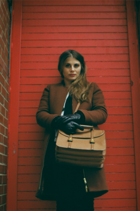film photograph portrait young woman long hair blonde bokeh red door leather gloves purse handbag