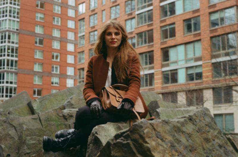 film photograph portrait young woman long hair blonde bokeh sitting rocks leather gloves handbag purse