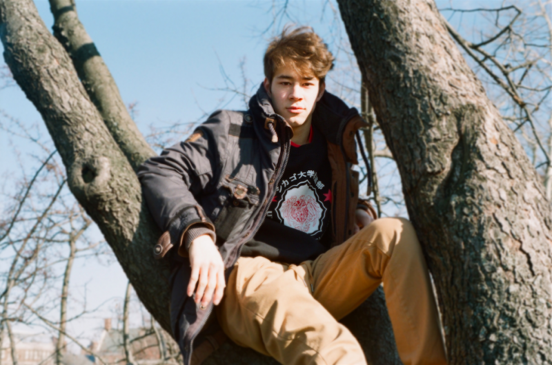film photograph portrait young man hapa sitting tree winter bare branches