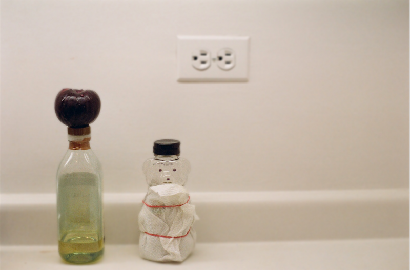 film photograph still life surreal plum olive oil honey bear bottle outlet white wall kitchen